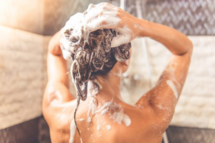 Vue arrière d'une belle jeune femme nue utilise du shampooing sans sulfate pendant qu'elle prend une douche dans la salle de bain